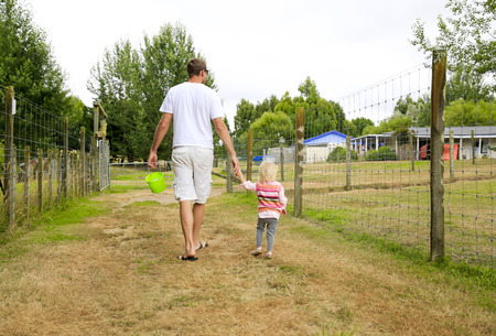 reisen: Father with daughter observing the farmland area through the wire fence. North Island New Zealand