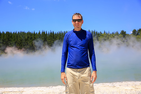 hydrothermal: Young happy man in blue shirt enjoying Champagne Poollandscape. Wai-O-Tapu Thermal Wonderland, New Zealand. Stock Photo