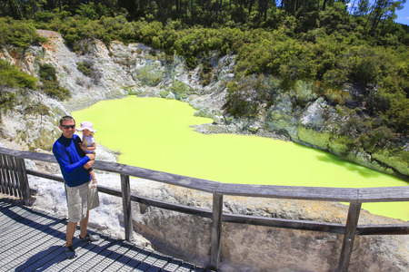 Young happy father with his cute little daughter  on enjoying landscape of Wai-O-Tapu thermal area, New Zealand Stock Photo