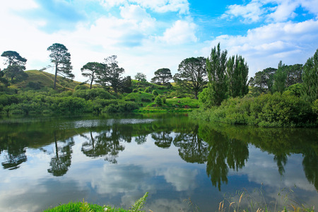 saga: MATAMATA, NEW ZEALAND - JANUARY 15, 2015: Hobbiton - movie set created for filming the Lord of the Rings. View of pond with amazing landscape.