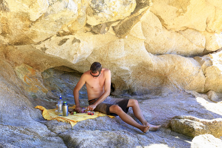Hungry young man is going to have lunch, sitting in unusual rock Formations of Tonga Arches of New Zealand Stock Photo
