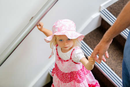 Charming little caucasian girl in pink floral dress looking up Zdjęcie Seryjne
