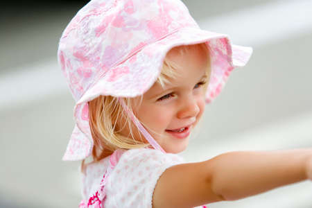 Charming little caucasian girl in pink hat smiling Zdjęcie Seryjne