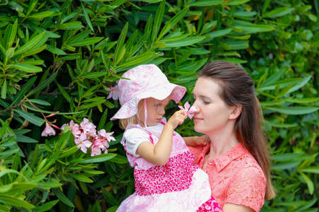 Cute daughter present her mother the pink flower and happy mother smelling it with enjoying face on green summer