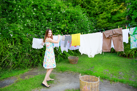 woman clothes: Smiling young woman in colorful dress hanging laundry on clothesline at the backyard Stock Photo