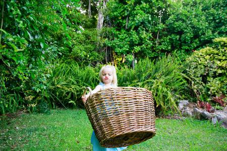 Little girl in a blue dress carrying big empty wicker laundry basket