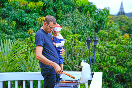 Young loving father and his cute little daughter, adorable girl wearing nice knitted hat, barbecuing chicken meat on the grill on backyard deck.