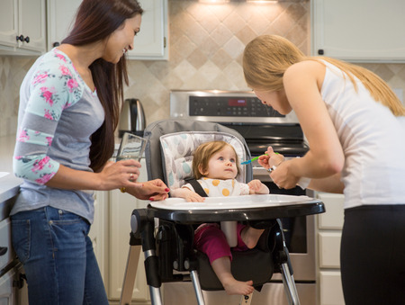adorable child: Two happy young women feed the child with a spoon. Adorable little baby girl is sitting in highchair. Kitchen interior