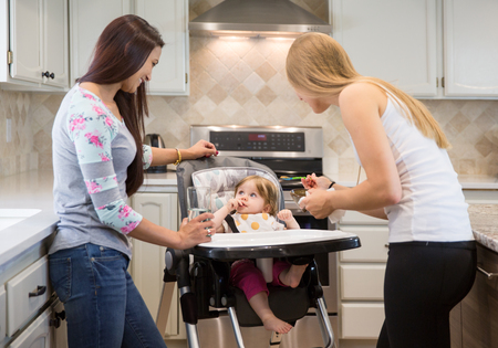 highchair: Two happy young women feed the child with a spoon. Adorable little baby girl is sitting in highchair. Kitchen interior