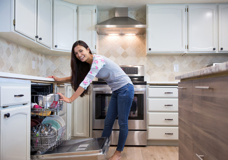 happy young woman putting dishes into the dishwasher in her modern kitchen