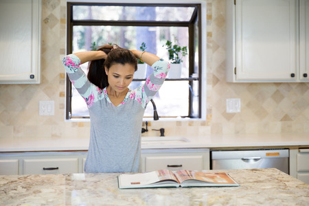 together with long tie: Young housewife is tying her hair before cooking dinner, while looking into a cookbook in the kitchen