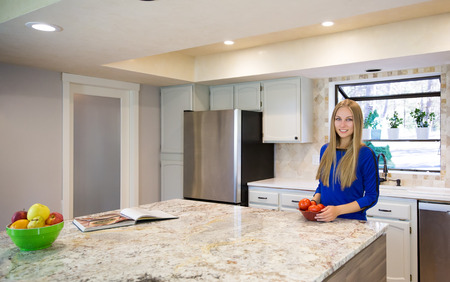 counter top: Attractive young blond-haired smiling woman holding a bowl of tomatoes, prepared for vegetable salad, staying by the kitchen island with marble counter top.