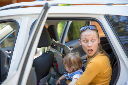 Surprised young woman with big eyes and with cute little girl in her hands ,ready to exit the car, see something scareful, unexpected Imagens