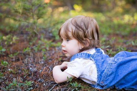山の森の中彼女の顔を地面に横たわって愛らしい幼児の女の子 写真素材