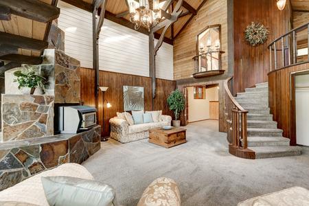 Modern houten huisje interieur met woonkamer close-up. Prachtige open haard met natuursteen tegels trim en wenteltrap. Northwest, USA Stockfoto