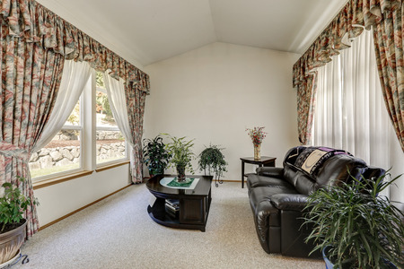 Cozy sitting area with elegant window curtains and vaulted ceiling. Black furniture set and lots of pots with green plants around. Northwest, USA