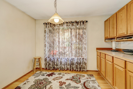 Empty dining room interior with window curtain, colorful rug and wooden cabinets. Northwest, USA