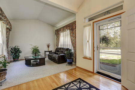 entryway: Cozy sitting area with elegant window curtains and vaulted ceiling. Black furniture set and lots of pots with green plants around. The room connected with entryway. Northwest, USA