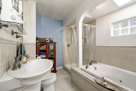 Salle de bain blanche et propre avec carrelage beige et petite fenêtre,  baignoire et douche. Northwest, États-Unis