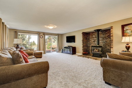 Large and spacious living room, brick wall with fireplace, soft carpet floor, comfortable sofas and exit to back yard. Northwest, USA Stock Photo