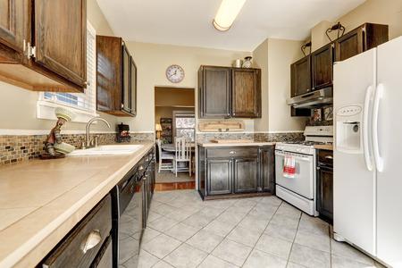 Kitchen room - dark brown cabinets, tile floor and white appliances. Northwest, USA