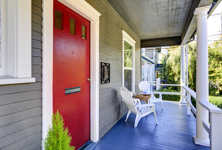 Entrance porch with white columns, blue wooden floor and red front  door. Northwest, USA