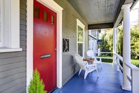 porche de entrada con columnas blancas, suelo de madera azul y puerta roja. Noroeste, EE.UU.