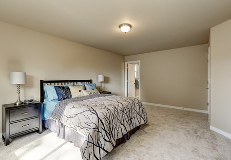 second floor: Simple design interior of beige Womans bedroom on the second floor. There is large bed, two nightstands and soft carpet floor. Northwest, USA