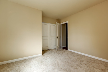 Opened door to an Empty beige room with carpet floor and a closet.  Northwest, USA Stock Photo