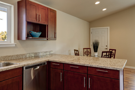 cabinets: View of burgundy kitchen cabinets with granite counter top and dining area. House interior. Northwest, USA