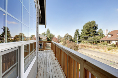 neighboring: Long wooden empty balcony overlooking the road and neighboring houses. Northwest, USA Stock Photo