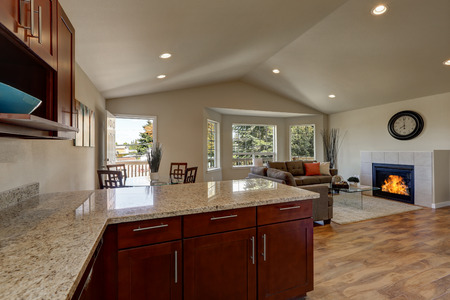 areas: Open floor plan of kitchen, dining and living rooms with hardwood floor and vaulted ceiling. House interior. Northwest, USA Stock Photo