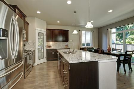 Groot kookeiland met granieten aanrechtblad en laden in een moderne open plattegrond keuken. Zijaanzicht van nieuwe roestvrij staalkoelkast. Noordwesten, de VS
