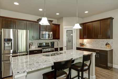 granite: Classic kitchen room interior with large kitchen island with granite counter tops,  modern cabinets, stainless steel appliances and pantry. Northwest, USA Stock Photo