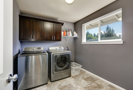 laundry room: Grey laundry room with modern stainless steel washing machine and dryer, brown cabinets and  tile floor. Northwest, USA Stock Photo