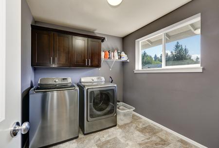 Lavadero gris con la moderna máquina de acero inoxidable lavadora y secadora, armarios de color marrón y suelo de baldosas. Noroeste, EE.UU. Foto de archivo - 64698697