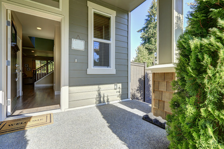 Entrance porch of American gray house with open front door with welcome mat on a sunny day. Northwest, USA