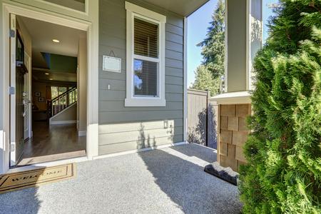 Eingangsportal des amerikanischen grauen Haus mit offener Fronttür mit Fußmatte an einem sonnigen Tag. Northwest, USA Standard-Bild - 67033474