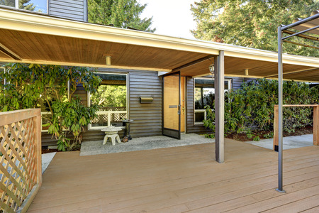 Open entrance door and empty wooden walkout deck. House exterior. Northwest, USA Stock Photo