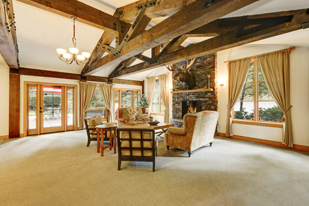 Apartment building lobby with soft area.  Cozy room with high ceiling and wooden beams, Stone tile wall with fireplace and moose head.  Northwest, USA