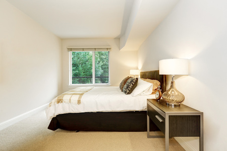 nightstands: Neat bedroom with a bed and nightstands with lamps. Carpet floor and white walls. Northwest. USA
