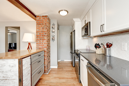White kitchen room interior with grey details. White backsplash , glossy counters , small kitchen island designed in old style and red brick accent wall . Northwest, USA