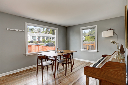 dining table and chairs: Gray dining room interior with piano and wooden table and four chairs. Northwest, USA