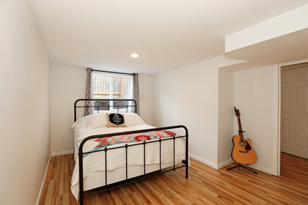 patchwork quilt: Small white bedroom with black iron bed and colorful patchwork quilt on it and guitar standing in the corner. Northwest, USA