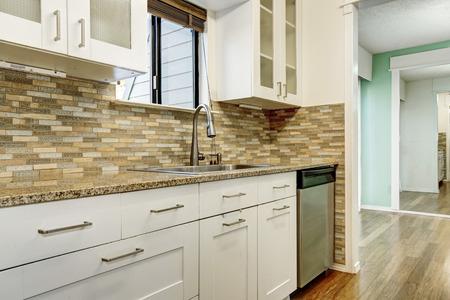 splash back: Modern white cabinets and brown mosaic back splash in apartment. Northwest, USA