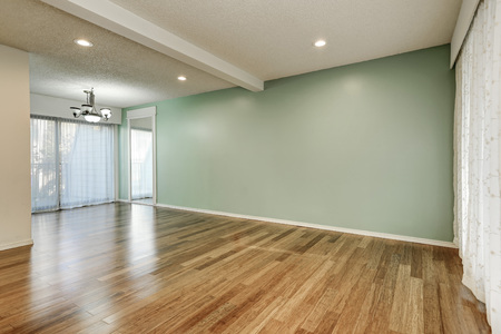 Green and mint interior of empty room with large floor to ceiling windows and shiny hardwood floor in new apartment. Northwest, USA