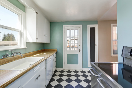 Mint walls and white and black square tiled floor in old style kitchen with retro details. Northwest, USA