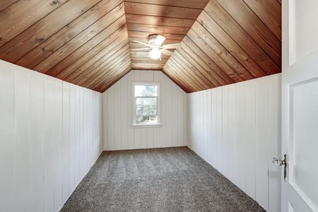 remodeled: Small empty attic room with wood paneling, carpet floor and vaulted ceiling. Northwest, USA Stock Photo