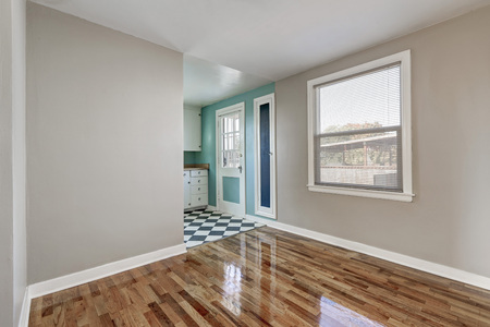 empty room background: Empty beige room with hardwood floor in old empty house. Mint kitchen walls in the background. Northwest, USA Stock Photo