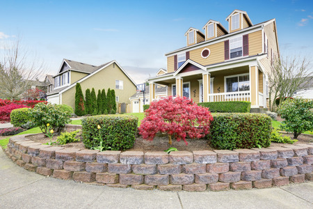 Amerikaans huis buitenkant met overdekte veranda en kolommen. Mooie uitstraling en perfect landschapsontwerp. Northwest, VS.